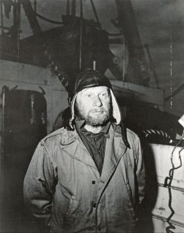 """Original Caption: Destroy German radio base in Greenland. This German prisoner, """"Dr. Sennse, takes a long look from the deck of the U.S. Coast Guard Cutter at the site of the captured German army radio base on the Greenland shore. He was captured by U.S. soldiers and Coastguard's me, operating as a task force, when he came back to the base shortly after the Americans landed. He'd been building a grave over the body of who had been a member of the Danish scouting party that discovered the German base. Local Identifier: 26-G-09-21-43-9 (Box44)"""