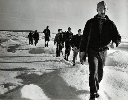 Original Caption: The Coast guard sends landing force into Greenland to capture Nazi weather base. Plodding over snow and ice-covered wastes on Shannon Island, Greenland, a Coast Guard landing force, ashore from a Combat Cutter, moves against the a Nazi weather station. All guns aboard the cutter were manned when the German camp was spotted in the distance. The Coast Guardsmen found the base deserted. It was destroyed after some equipment had been salvaged. Later operations by the Coast Guard led to the liquidation of another German Greenland base, the capture of several prisoners and the taking of an enemy trawler. Local Identifier: 26-G-2960 (Box 45)