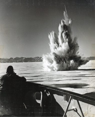 Original Caption: Coast Guard blasts a passage in hunt for Nazi Greenland base. Demolition charges toss a spectacular geyser of ice and water as the crew of a Coast Guard combat cutter blasts its way toward a remote stretch of Greenland's east coast on a hunt for hidden German radio-weather stations. Knocking out two of these stations rewarded the Coast Guard's Greenland Patrol in ten weeks of intensive action among the ice flows. Sixty Germans were captured, one armed trawler was captured, another was scuttled by its crew. Four Coast Guard combat cutters participated in the dramatic series of incidents up in the Arctic. Local Identifier: 26-G-2962 (Box45)