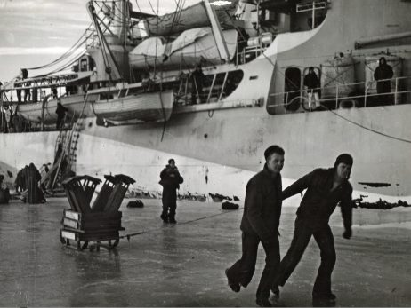 Original Caption: Captured Nazi supplies delivered by coast guard to Greenland patrol. Supplies taken at a Nazi radio-weather station on the northeast coast of Greenland are turned over to the Danish sled patrol by Coast Guardsmen from the combat cutter, Eastwind, which engineered the surprise raid. Twelve Germans surrender without a fight. Later, two Coast Guard combat cutter teams to surprise and capture intact a German trawler, built in 1944, that was caught in the ice pack nearby. Twenty crewmen were added to the prisoner haul and the ship was salvaged from the ice. Local Identifier: 26-G-2994 (Box 45)