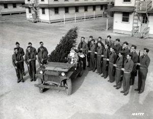 """Photo ID: 111-SC-126777. Original caption: """"Just before Santa Claus leaves his """"jeep-sleigh"""" the guard of honor stands on each side presenting arms to the Christmas visitor. Camp Lee, Virginia, Quartermaster Replacement Center."""" Photo by: Larry Williams. Date: December 1941"""