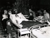 """Photo ID: 111-SC-199278. Original caption: """"French orphans at a Christmas party given by a United States Army Hospital in Paris crowd around patient Sgt. Charles Sipe (646 Homeplace Avenue, Indianapolis, Indiana). A good time was had by all."""" Photo by: 48th General Hospital, Paris, France. Date: December 25th, 1944"""
