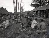 """Photo ID: 111-SC-262133. Original caption: """"GIs eat a turkey Christmas dinner while other GIs wait in line for their chow, near the front lines on Mindoro Island, Philippine Islands."""" Photographer: Pvt. Ben Gross. Date: December 25th, 1944"""