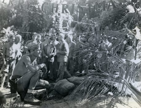 """Photo ID: 127-GW-1117-74821. Original caption: """"Longing for home is Top Sgt. Tom Dameron as he looks at the Christmas tree his Company has put up. Bougainville."""" Photographer: Sgt. R. Robbins. Date: December 25th, 1943"""