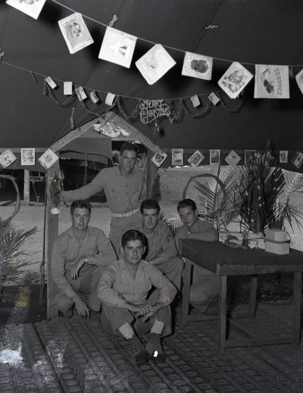 """Photo ID: 127-N-104420. Original caption: """"Guadalcanal. With a Christmas tree, wreaths, and tent decoration laboriously constructed from palm fronds, Christmas cards and package wrappings, these Marines brought the Christmas atmosphere into their tent at this Pacific base. Front seated: Private First Class Leonard J. Virgili (22 years old, 1107 Corbin Street, Rockford, Illinois). Second row kneeling: Private First Class William R. Barkley (21 years old, 8329 Cregier Avenue, Chicago, Illinois); Corporal Robert L. Hill (22 years old, Route #1, Parkville, Missouri); Corporal Lonnie O. Counts Jr. (20 years old, 1200 Edgefield Avenue, Greenwood, South Carolina). Rear standing: Private First Class Clarence Janicki (24 years old, 3269 South Pine Avenue, Milwaukee, Wisconsin). Photographer: Sgt. Hewitt. Date: December 24th, 1944"""