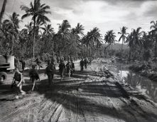 """Photo ID: 127-N-71430. Original caption: """"Marines leaving...Marines that landed on November 1 to establish a beachhead at Empress Augusta Bay march down a road hacked out of the jungle by SeaBees as they are relieved by Army forces. Many of them fought through this stretch of jungle to drive the Japanese back. Bougainville."""" Photographer: Sgt. W.G. Wilson. Date: December 25th, 1943"""