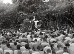 """Photo ID: 127-N-72375. Original caption: """"Christmas Eve...Marines, on the eve of the invasion of Cape Gloucester, attend Christmas church services on a SoPac island."""" Photographer: Sylvester. Date: December 25th-26th, 1943"""