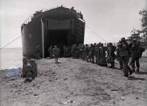 """Photo ID: 127-N-72376. Original caption: """"Marines board LST on Christmas Day for Cape Gloucester. Oro Bay."""" Photographer: Sylvester. Date: December 25th, 1943"""