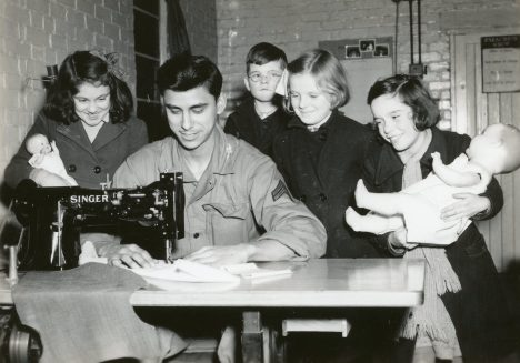 """Photo ID: 342-FH-3A-14327-123806AC. Original caption: """"Wishing to ensure the children of England a Merry Christmas, Cpl. Anthony Perez, of Los Angeles, utilizes his """"off duty"""" hours by making dresses and other cloth toys. Serving as a parachute folder and repair man at his fighter-repair base, Cpl. Perez enjoys the company of some his little friends while he works on their gifts."""" Date: December 1944"""