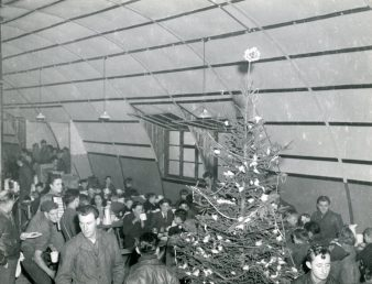 """Photo ID: 342-FH-3A-14449-65542AC. Original caption: """"The Christmas tree adds a festive note to the party given for British children by men of the 401st Bomb Group at an 8th Air Force base in England."""" Date: December 25th, 1943"""