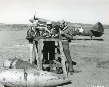 """Photo ID: 342-FH-3A-2359-74184AC. Original caption: """"While still on alert duty, S/Sgt. J.A. Muller, Cpl. John W. Coleman, and Cpl. L.B. Thomas of the 16th Fighter Squadron, 51st Fighter Group, consume their Christmas dinner on the field at a base somewhere in China."""" Photo by: 7th Photo Tech. Squadron, 8th Reconn. Group. Date: December 25th, 1942"""