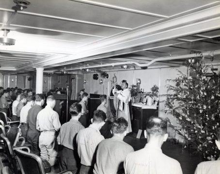 "Photo ID: 80-G-207819. Original caption: ""Divine service on the USS Enterprise (CV-6) on Christmas Day. Catholic Midnight Mass: the chaplain is Rev. Felix Reitlingshofer, Lt., a Franciscan friar."" Date: December 25th, 1943"