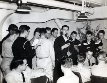 "Photo ID: 80-G-209233. Original caption: ""Celebrating Christmas Eve on board the USS Core (CVE-13) while at sea. Officers and men join in singing Christmas carols in the wardroom. Left to right: PTR3c RW West; Lt. (jg) LA Luft Jr.; S2C RL Hudson; Lt. (jg) LB Schultz; Lt. (jg) ES Eichin; Ens. HNR Brookings; Chaplain TT Shea; S2c S. Schwartz; SK3c EG Knoll; AOM3c RC Cambell; Navy Technician R. Murphy."" Date: December 24th, 1943"