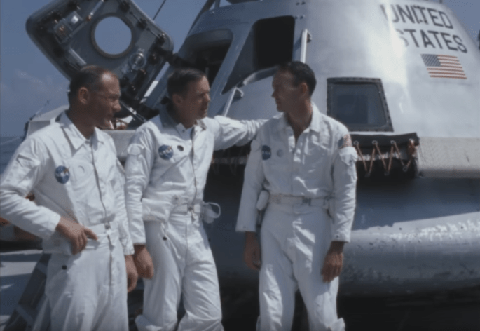 Astronauts Buzz Aldrin, Neil Armstrong, and Michael Collins standing in front of the Apollo 11 command module.