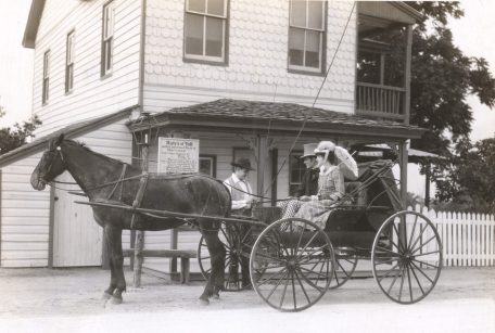 In 1875, young Jim the toll-gate keeper collects payment from two travelers. Photo number 30-N-40-490.