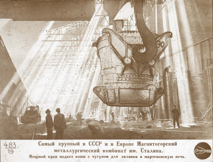 """""""The Stalin Magnitogorsk Iron and Steel Works is the largest [of its kind] in the USSR and in Europe. A powerful crane delivers a bucket of cast iron to fill the open-hearth furnace."""" From Series RS: Educational and Propaganda Slide Sets Created in the Soviet Union, 1945 – 1950; 242-RS-483-19"""