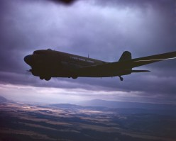 """342-C-K3710 NAID: 148728112 Original Caption: Operation Firefly - A C-47 of the First Troop Carrier Command flies over rough Oregon countryside. The plane will drop a """"stick"""" of fire-fighting paratroopers of the 555th Parachute Infantry. This is a joint operation of the AAF Troop Carrier Command, the US Forestry Service and the Parachute Infantry. The Parachutist operate in remote areas where it would take days for forestry men on the ground to reach the devastated areas."""