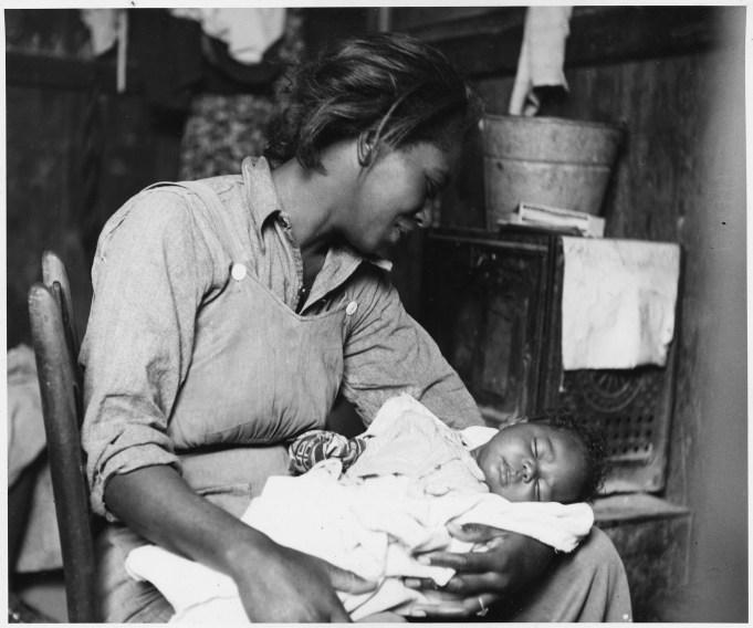 "Original Caption: ""Near Buckeye, Maricopa County, Arizona. Migrant [African-American] cotton picker and her baby."" Photographer: Dorothea Lange. Date: November 1940. Local ID: 83-G-44371 (NAID 522540)"