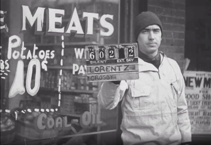 """A man stands in front of a store window reading """"MEATS Potatoes 10¢"""" and """"Coal-Oil"""". He is holding a slate that reads 602 2 SILENT EXT. DAY LORENTZ CROSBY"""" The man is wearing a knit cap and pullover."""