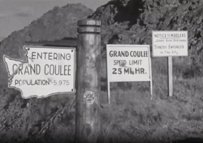 """Three road signs read """"Entering Grand Coulee Population 5,975,"""" """"Grand Coulee Speed Limit 25 MI. HR."""" and """"Notice to Peddlers Green River Ordinance Strictly Enforced in This City."""" A wooden post is in the center of the image and there is a mountain in the background."""