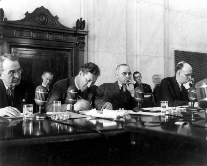 Four men sit in front of microphones at a hearing.
