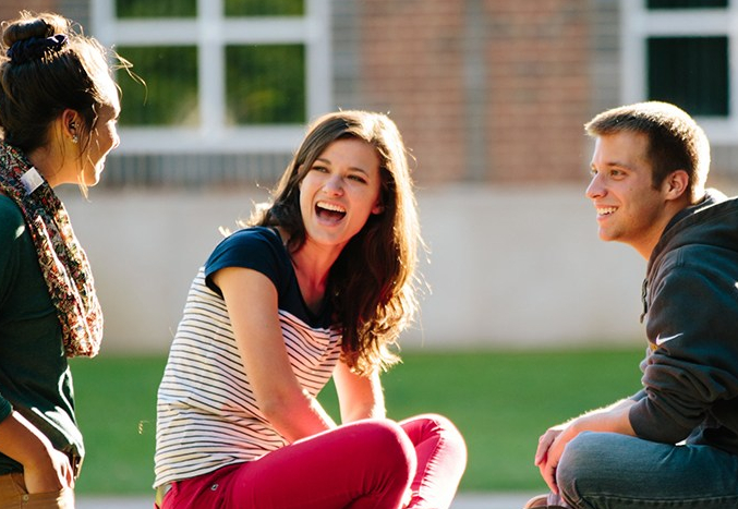 a young woman and young man sitting crossed-leg who have turned to talk to another young woman student. The weather is warm and the grass in the background is gree.