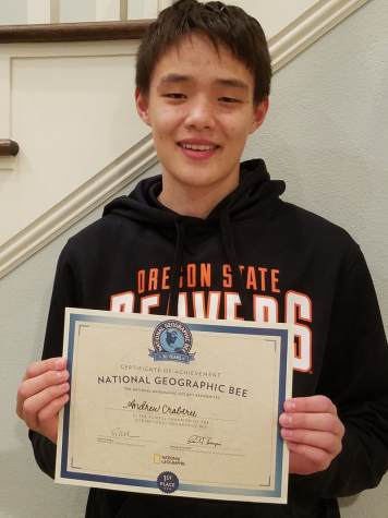 Andrew Crabtree (8) holding his certificate as the school champion of the 2018 National Geographic Bee.