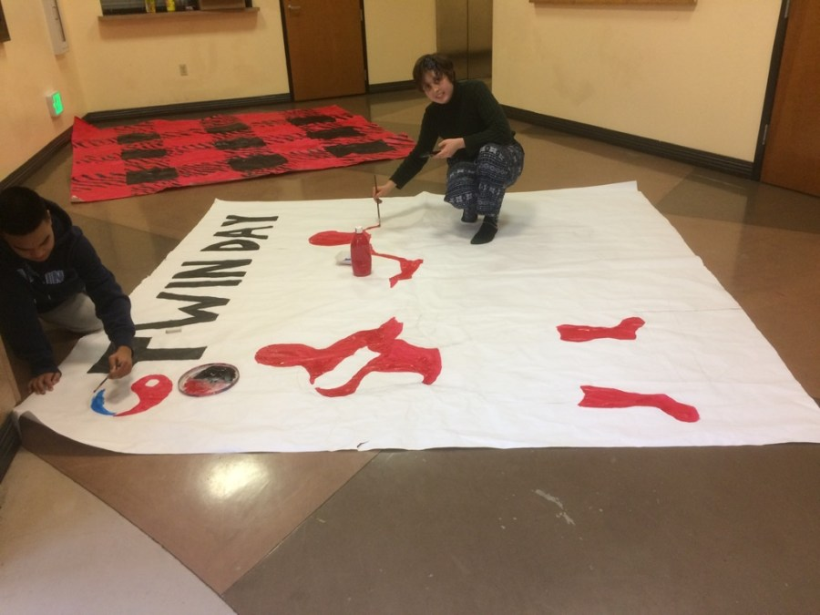 Kyle Lopez (12) and Adam Lawson (10) create the spirit day poster for Twin Day on Jan. 20. ASB members spend time painting the backdrop for each spirit day for students to use when taking photos.