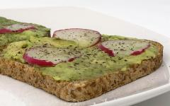 Radish avocado toast contains gluten free bread with mashed avocado, radish slices, salt, and pepper. It is a vegetarian food option.