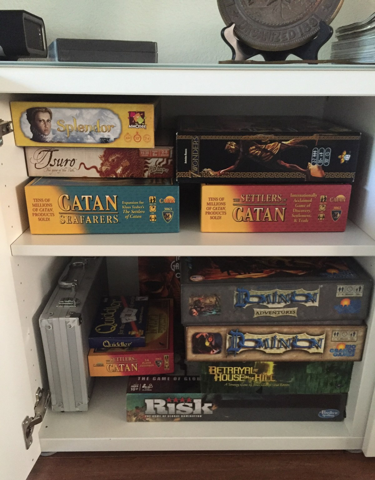 Game cabinet filled with games including Settlers of Catan for game night