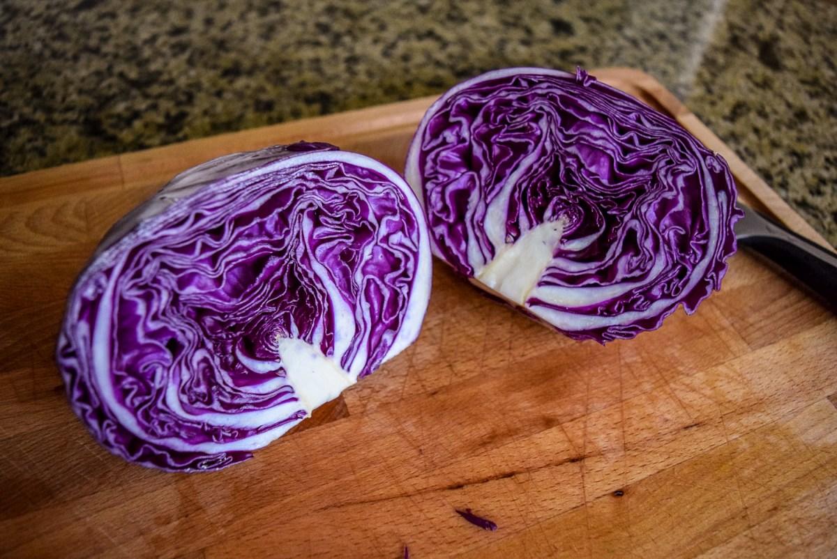 Red cabbage cut in half for Sunshine Spicy Mustard Tahini Cruciferous Slaw