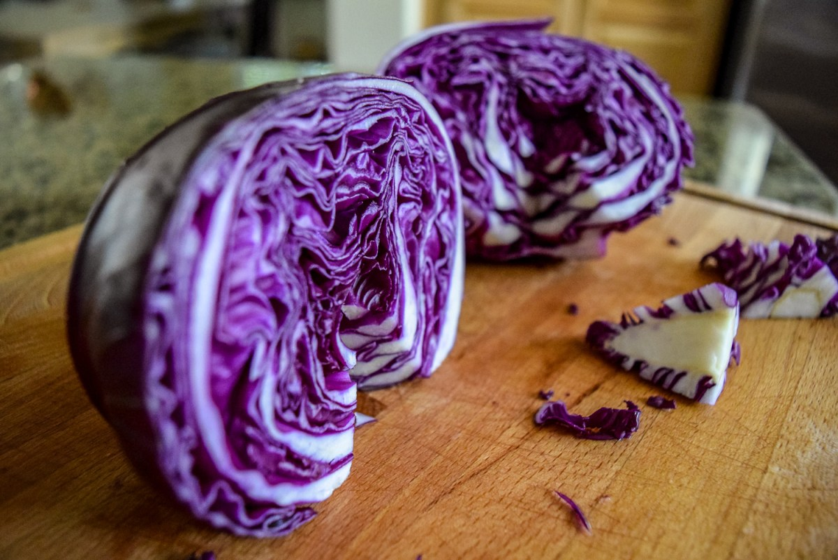 Cored red cabbage half for Sunshine Spicy Mustard Tahini Cruciferous Slaw