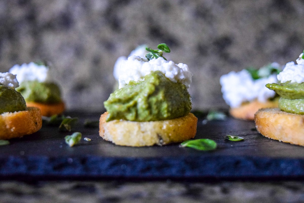 Marjoram Pea Pesto Crostini with Fresh Ricotta on slate cheeseboard from side up close