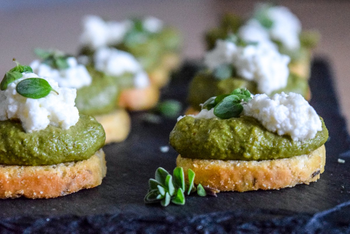 Finished Marjoram Pea Pesto Crostini with Fresh Ricotta up close from front on slate cheese board