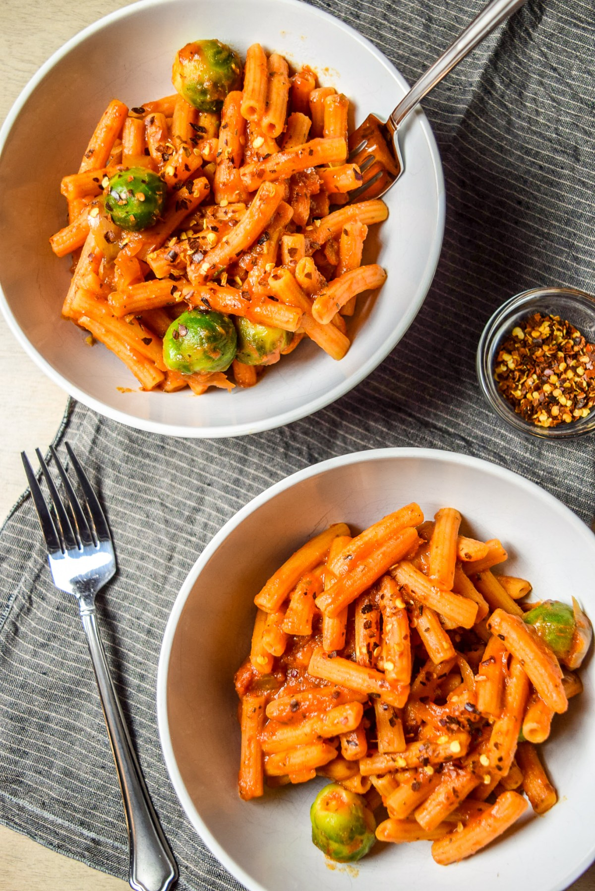 Finished Protein-Packed Red Lentil Pasta with Marinara, Brussel Sprouts, and Caramelized Onions in two bowls with forks, napkin, and chili pepper flakes from top