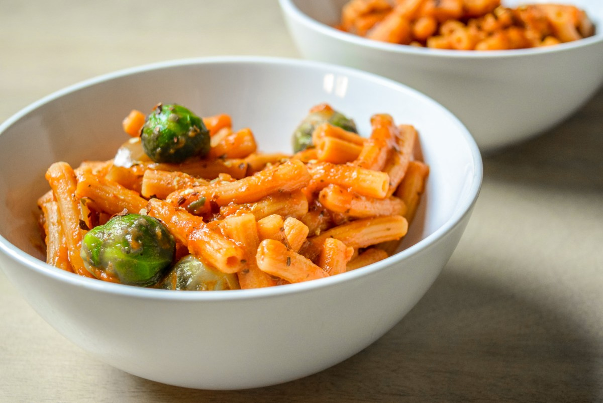 Finished Protein-Packed Red Lentil Pasta with Marinara, Brussel Sprouts, and Caramelized Onions in two bowls up close