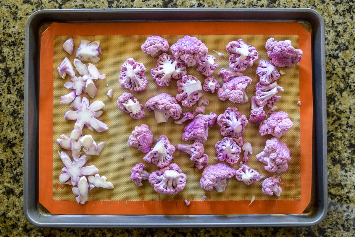 Raw purple cauliflower cut up stem pieces and florets on silicone baking sheet on calphalon baking sheet from top