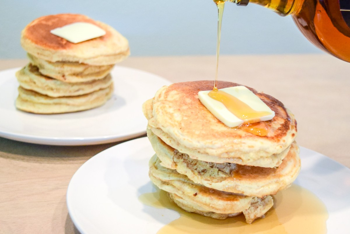 Pouring maple syrup onto Trader Joe's Multigrain Pancake Mix stack with butter