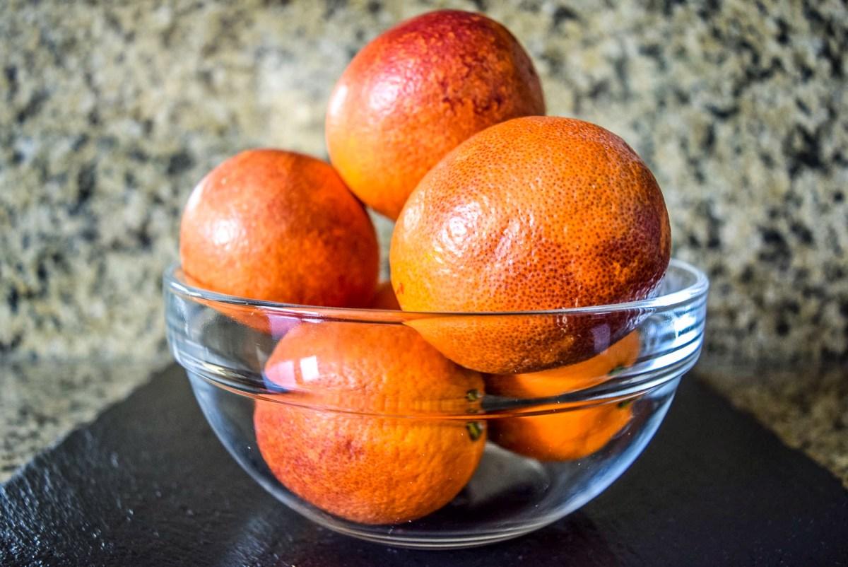 Glass bowl of blood oranges on slate cheesboard