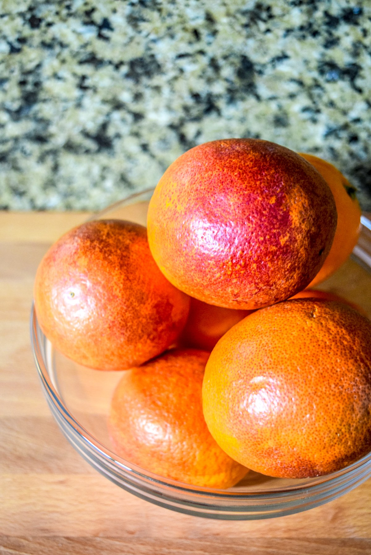 Glass bowl of blood oranges on wooden cutting board