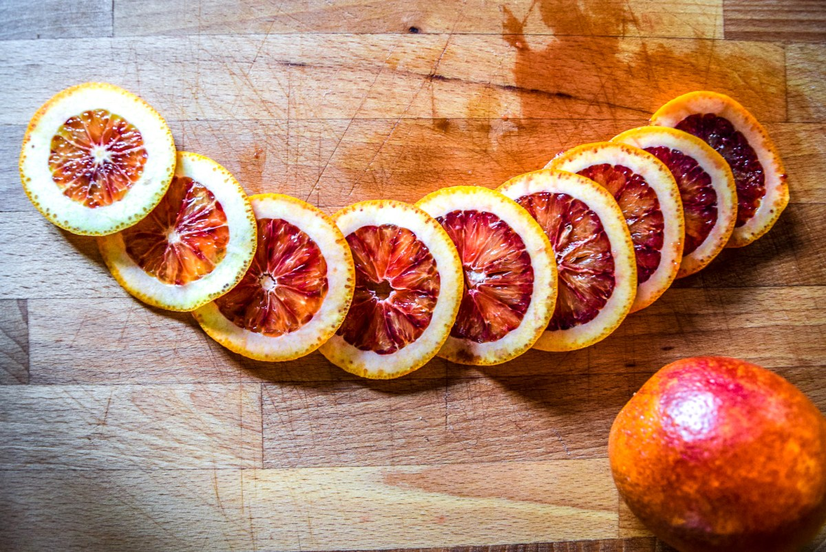 Sliced blood orange rounds in preparation for candying from top
