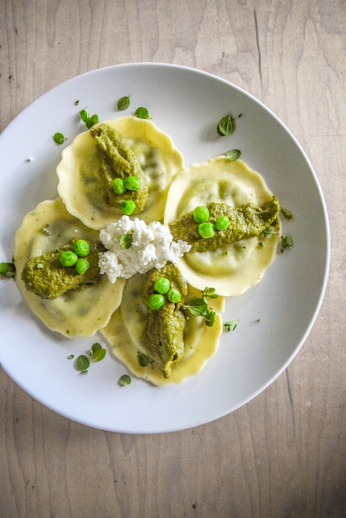 Marjoram Pea Pesto Ricotta Ravioli on plate from top vertical