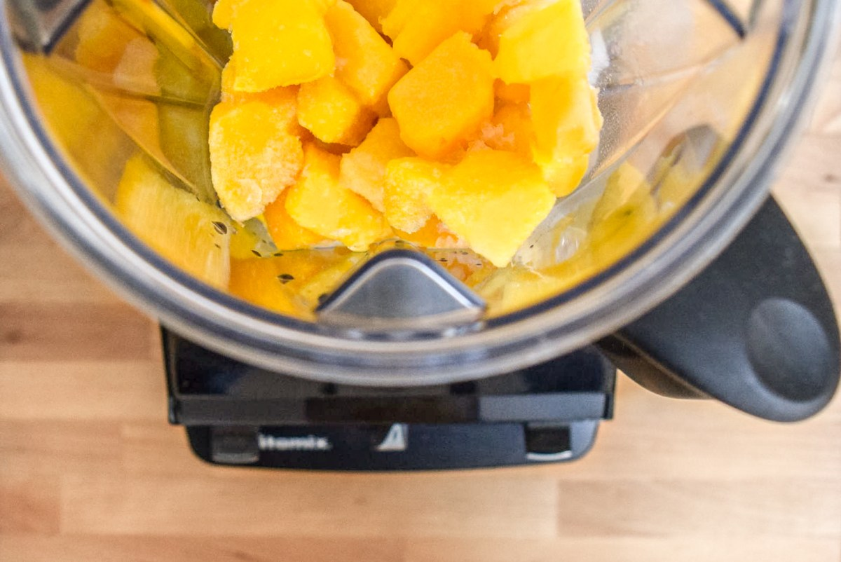 Frozen mango pieces and almond milk in Vitamix blender from top for Two-Ingredient Almond Mango Ice Cream