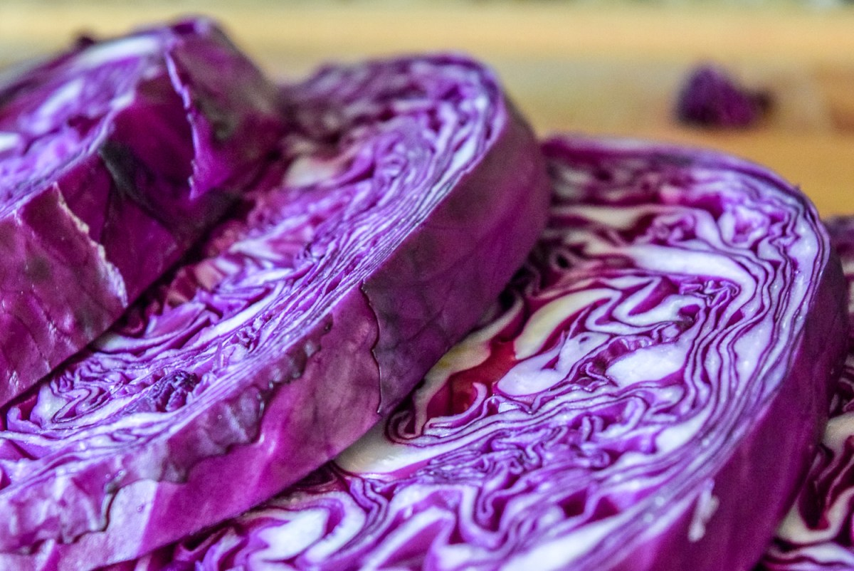 Sliced red cabbage steaks on wooden cuttingboard from side up close