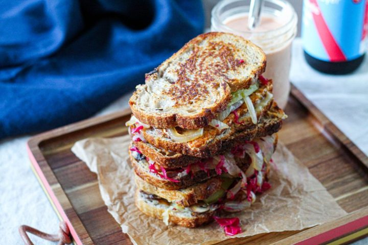 horizontal shot of a stack of 3 Reubens on a wooden board