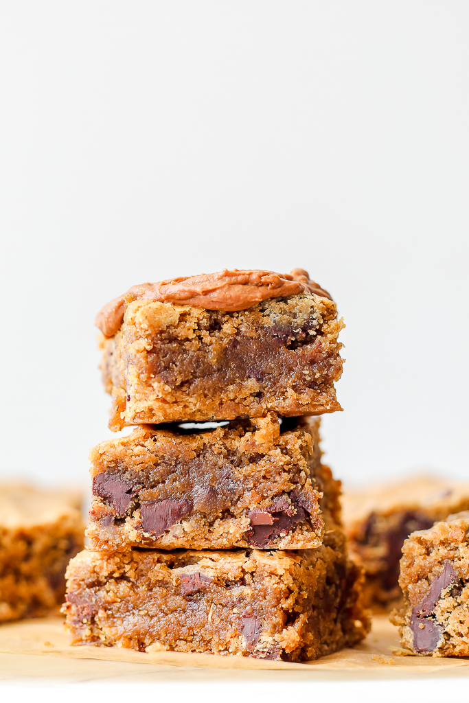 straight on shot of three vegan chocolate chunk cashew butter blondies on a white marble board