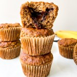 a straight on shot of three vegan banana Nutella Muffins on a white plate