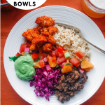 overhead shot of a burrito bowl on a dark orange backdrop with a glass of beer on the upper right side
