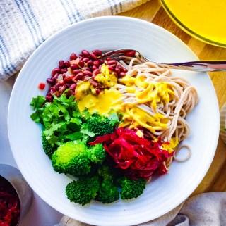A healthy macrobiotic bowl with soba noodles, steamed broccoli, beet sauerkraut, marinated adzuki beans, cilantro, and a turmeric tahini sauce.