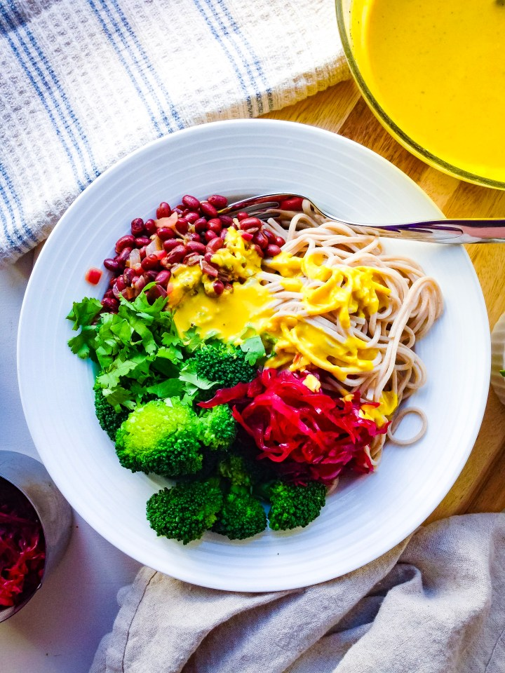 A healthy vegan macrobiotic bowl with soba noodles, steamed broccoli, beet sauerkraut, marinated adzuki beans, cilantro, and a turmeric tahini sauce.